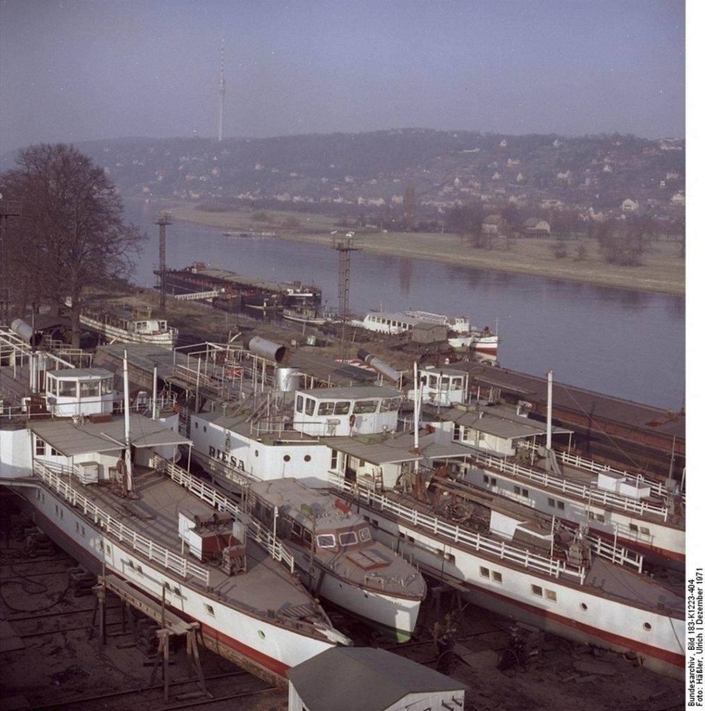 """ADN-ZB / Häßler 21.12.71 [Herausgabedatum] Dresden: """"Weiße Flotte"""" im Winterquartier. Rund 2,5 Millionen Fahrgäste hat die """"Weiße Flotte"""" der Elbestadt in der vergangenen Schifffahrtssaison befördert. Auf der 105 Kilometer langen Strecke verkehrten 19 Dampf- und Dieselschiffe. Sie legten dabei 280.00 km zurück. Jetzt warfen die Schiffe in ihrem Winterquartier Anker. Einige nahmen Kurs auf die Schiffswerft Dresden-Laubegast, um in Trockendocks generalüberholt zu werden."""